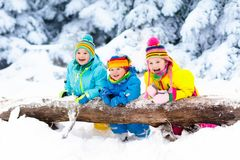 Kids playing in snow. Children play outdoors in winter snowfall. Kids playing in snow. Children play outdoors on snowy winter day. Boy and girl catching Stock Image