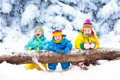 Kids playing in snow. Children play outdoors in winter snowfall. Royalty Free Stock Photography