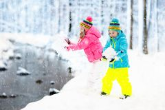Kids playing in snow. Children play outdoors in winter snowfall. Kids playing in snow. Children play outdoors on snowy winter day. Boy and girl catching Royalty Free Stock Photos