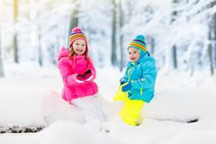 Kids playing in snow. Children play outdoors in winter snowfall. Kids playing in snow. Children play outdoors on snowy winter day. Boy and girl catching Royalty Free Stock Photography
