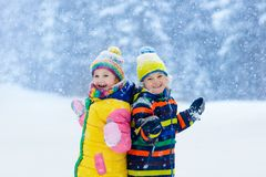 Kids playing in snow. Children play in winter. Kids playing in snow. Children play outdoors on snowy winter day. Boy and girl catching snowflakes in snowfall royalty free stock photo