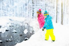 Kids playing in snow. Children play outdoors in winter snowfall. Stock Images