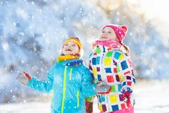 Kids winter snow ball fight. Children play in snow. Kids playing in snow. Children play outdoors on snowy winter day. Boy and girl catching snowflakes in Stock Images