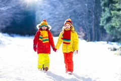 Kids winter snow ball fight. Children play in snow. Kids playing in snow. Children play outdoors on snowy winter day. Boy and girl catching snowflakes in royalty free stock photo