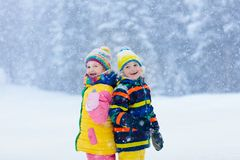 Kids playing in snow. Children play in winter. Kids playing in snow. Children play outdoors on snowy winter day. Boy and girl catching snowflakes in snowfall stock photography