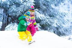 Kids playing in snow. Children play outdoors in winter snowfall. Stock Photo