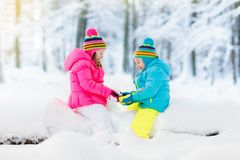 Kids playing in snow. Children play outdoors in winter snowfall. Stock Photos