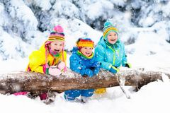 Kids playing in snow. Children play outdoors in winter snowfall. Kids playing in snow. Children play outdoors on snowy winter day. Boy and girl catching stock photography
