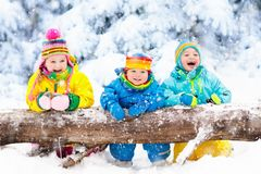 Kids playing in snow. Children play outdoors in winter snowfall. Stock Photography