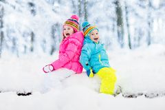Kids playing in snow. Children play outdoors in winter snowfall. Kids playing in snow. Children play outdoors on snowy winter day. Boy and girl catching Stock Photos