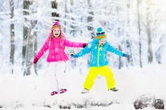 Kids playing in snow. Children play outdoors in winter snowfall. Royalty Free Stock Photos
