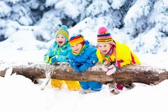 Kids playing in snow. Children play outdoors in winter snowfall. Kids playing in snow. Children play outdoors on snowy winter day. Boy and girl catching Royalty Free Stock Image