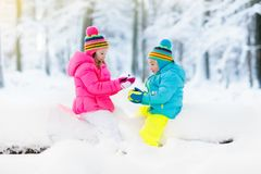 Kids playing in snow. Children play outdoors in winter snowfall. Royalty Free Stock Images