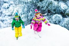 Kids playing in snow. Children play outdoors in winter snowfall. Royalty Free Stock Photo