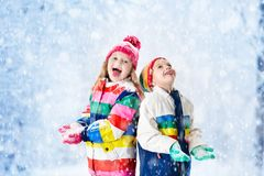 Kids playing in snow. Children play outdoors in winter snowfall. Kids playing in snow. Children play outdoors on snowy winter day. Boy and girl catching stock photo
