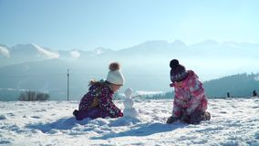 Children in outwear making small snowman while playing on snowy field in sunlight with mountains on background