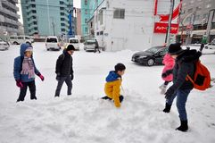 Kids are playing snow together near the road and building as background with lots of snow in Sapporo city, Japan January 21,2018. Photo of kids are playing snow royalty free stock images