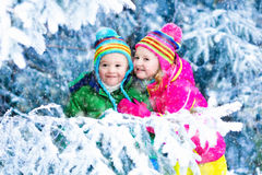Kids playing in snowy forest. Children play in snowy forest. Toddler kids outdoors in winter. Friends playing in snow.  vacation for  with young children. Little Royalty Free Stock Images