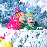 Kids playing in snowy forest. Children play in snowy forest. Toddler kids outdoors in winter. Friends playing in snow.  vacation for  with young children. Little Royalty Free Stock Image