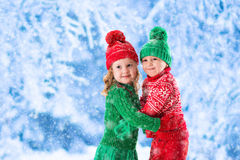 Kids playing in snowy winter forest Stock Image