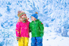 Kids playing in snowy winter park Stock Photography
