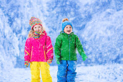 Kids playing in snowy winter park Stock Photos