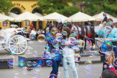 Kids playing with soap bubbles in city square royalty free stock image