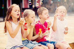 Kids playing with soap bubbles Stock Images