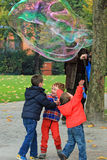 Kids playing with the soap bubbles in London Royalty Free Stock Images