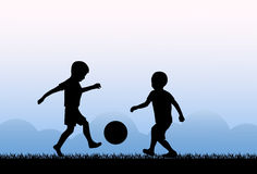 Kids playing soccer. Two small boys kicking a ball on the grass Royalty Free Stock Photos