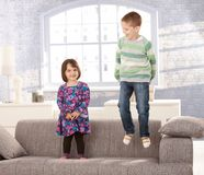 Kids playing on sofa Stock Photos