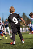 Kids playing soocer. Kids playing soccer outdoors on a sunny day. Trademarks have been removed Royalty Free Stock Photography