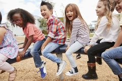 Kids playing on a spinning carousel in their schoolyard royalty free stock photography