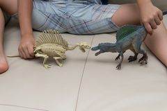 Kids playing a Spinosaurus toy and Spinosaurus skeleton Royalty Free Stock Image