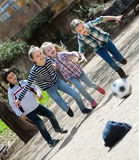 Kids playing street football outdoors Stock Image