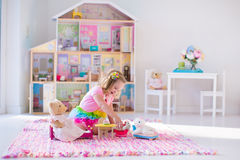 Kids playing with stuffed animals and doll house Stock Image