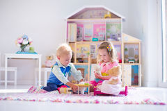 Kids playing with stuffed animals and doll house. Kids playing with doll house and stuffed animal toys. Children sit on a pink rug in a play room at home or Royalty Free Stock Images