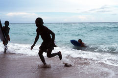 Kids playing in surf. Kids surfing, swimming on beach Royalty Free Stock Images