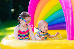 Kids playing in swimming pool Stock Images
