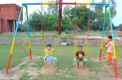 Kids playing with swing. Kids in India playing with swing in evening time Royalty Free Stock Image