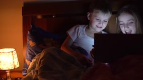 Kids playing tablet in bed. Cute kids playing tablet in bed stock footage