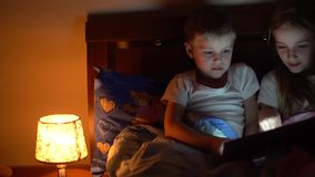Kids playing tablet in bed. Cute kids playing tablet in bed stock video