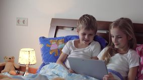 Kids playing tablet in bed. Cute kids playing tablet in bed stock video footage