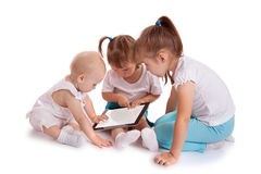 Kids playing with tablet computer. Three little kids playing with tablet PC computer on white background. Baby hand pointing on  touch screen Stock Photos