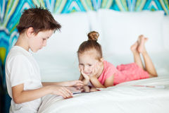 Kids playing on tablet device Royalty Free Stock Images