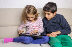 Kids playing on tablet pc at home Stock Image