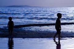 Kids playing on te Beach. Kids playing on the beach - silhouette shot Stock Images