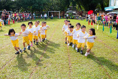 Kids playing teamwork racing. KUALA LUMPUR - 15 AUGUST 2010 : Unidentified children doing a teamwork racing at Taman Midah Kindergarten sport day on 15 August Stock Images