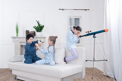 Kids playing with telescope and looking out window Stock Photos
