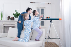 Kids playing with telescope and looking out window Royalty Free Stock Photo